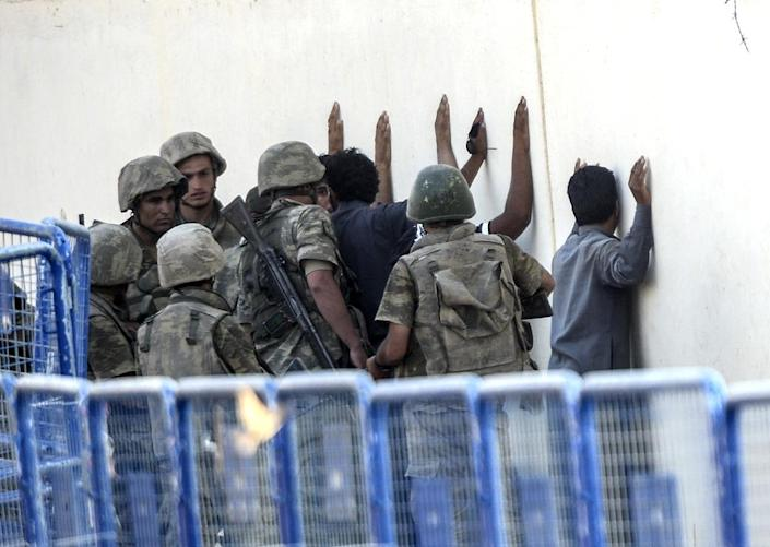 Turkish soldiers detain men from Syria, supposed to be Islamic State fighters, near the Akcakale crossing gate between Turkey and Syria on June 15, 2015 (AFP Photo/Bulent Kilic)