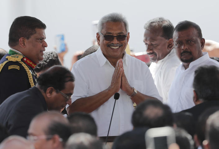 Sri Lanka's newly elected president Gotabaya Rajapaksa greets people as he arrive for the swearing in ceremony held at the 140 B.C Ruwanweli Seya Buddhist temple in ancient kingdom of Anuradhapura in northcentral Sri Lanka Monday, Nov. 18, 2019. The former defense official credited with ending a long civil war was Monday sworn in as Sri Lanka's seventh president after comfortably winning last Saturday's presidential election. (AP Photo/Eranga Jayawardena)
