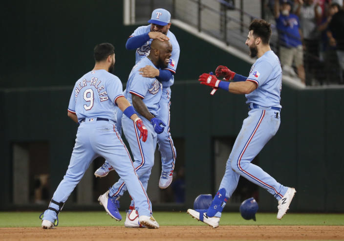 Texas Rangers' Adolis Garcia, bottom center, is hugged by Jose Trevino, top center, as Isiah Kiner-Falefa, left, and Joey Gallo, right, join in after a walk-off single against the Houston Astros in the tenth inning of a baseball game in Arlington, Texas, Sunday, May 23, 2021. (AP Photo/Ray Carlin)