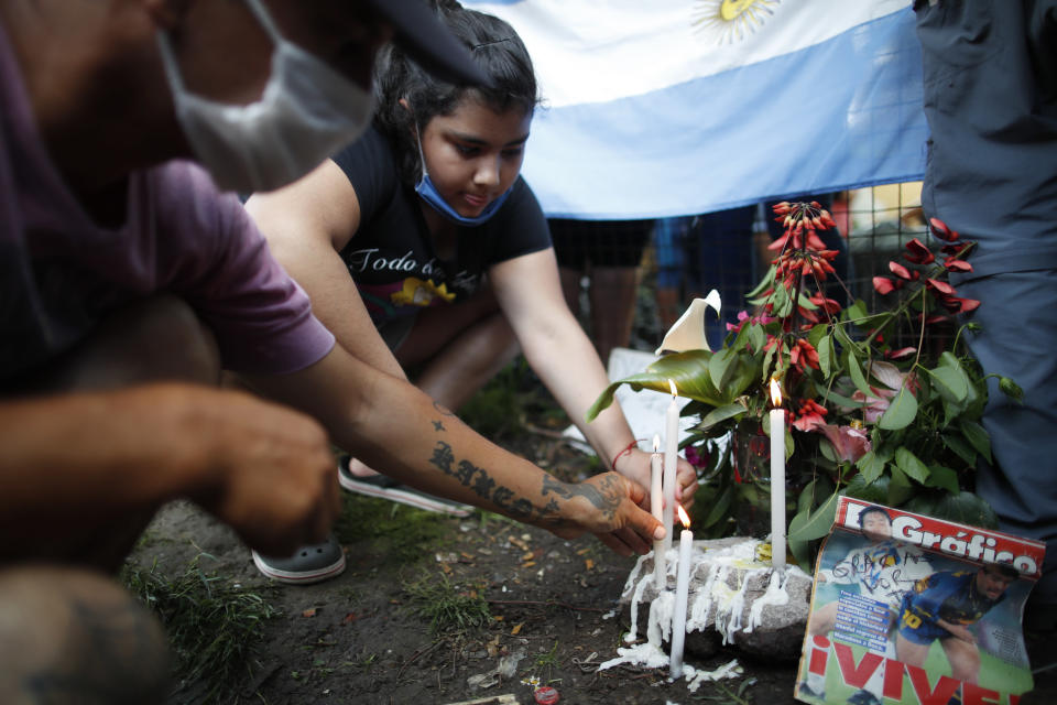 Neighbors light candles at the entrance the house where Diego Maradona was born in the Villa Fiorito neighborhood of Buenos Aires, Argentina, Wednesday, Nov. 25, 2020. Maradona, the Argentine soccer great who was among the best players ever and who led his country to the 1986 World Cup title before later struggling with cocaine use and obesity, died from a heart attack on Wednesday at his home in Buenos Aires. He was 60.(AP Photo/Natacha Pisarenko)