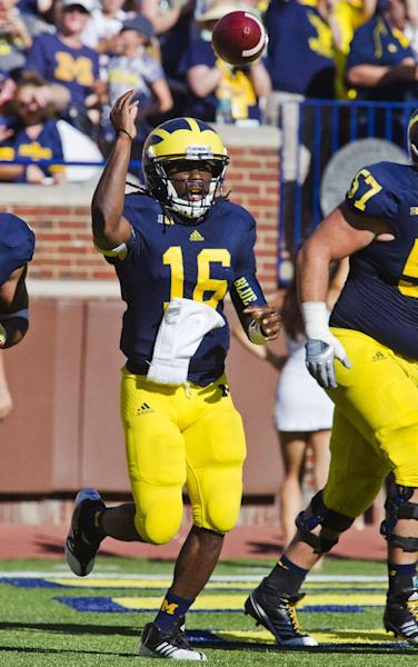 Michigan quarterback Denard Robinson (16) tosses the ball away after his 36-yard touchdown rush in the second quarter of an NCAA college football game against Massachusetts, Saturday, Sept. 15, 2012, in Ann Arbor, Mich. (AP Photo/Tony Ding)