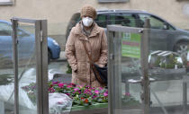 A woman with masks shops in a reopened store after lock down in Vienna, Austria, Monday, Feb. 8, 2021. The Austrian government has moved to restrict freedom of movement for people, in an effort to slow the onset of the COVID-19 coronavirus. (AP Photo/Ronald Zak)