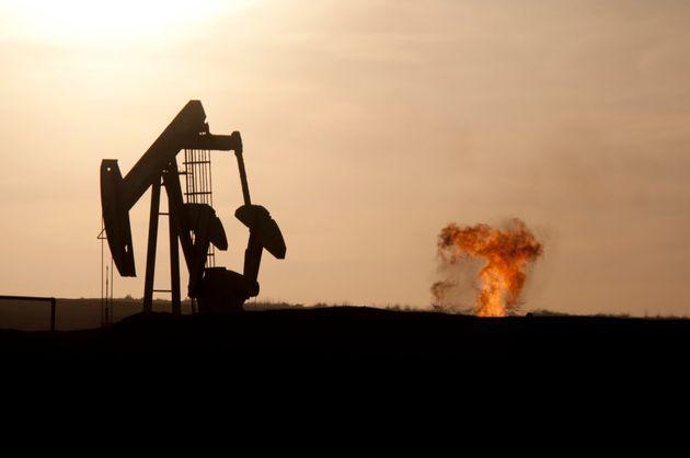 An oil well jack pump and a natural gas flare-off at sunset in the Bakken oil field north of Williston, North Dakota. (Photo: Photo by William Campbell/Corbis via Getty Images)