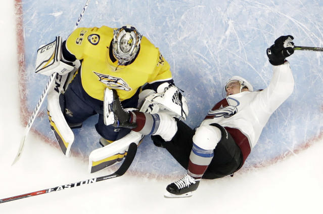 Colorado Avalanche defenseman Tyson Barrie (4) falls over Nashville Predators goalie Pekka Rinne (35), of Finland, during the second period in Game 2 of an NHL hockey first-round playoff series Saturday, April 14, 2018, in Nashville, Tenn. (AP Photo/Mark Humphrey)