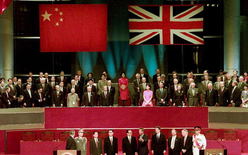 Leaders of China and Britain, including Chris Patten, stand to attention at the handover ceremony in 1997 - Jason Reed REUTERS