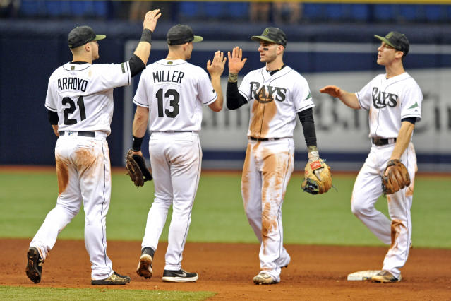 Tampa Bay Rays infielders Christian Arroyo, from left to right, Brad Miller, Daniel Robertson and Joey Wendle celebrate a 8-3 win over the Baltimore Orioles during a baseball game Sunday, May 27, 2018, in St. Petersburg, Fla. (AP Photo/Steve Nesius)