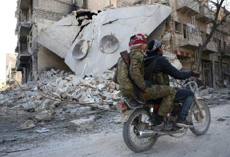 Rebels ride a motorcycle past a destroyed building in the northwestern Syrian border town of al-Bab on February 25, 2017