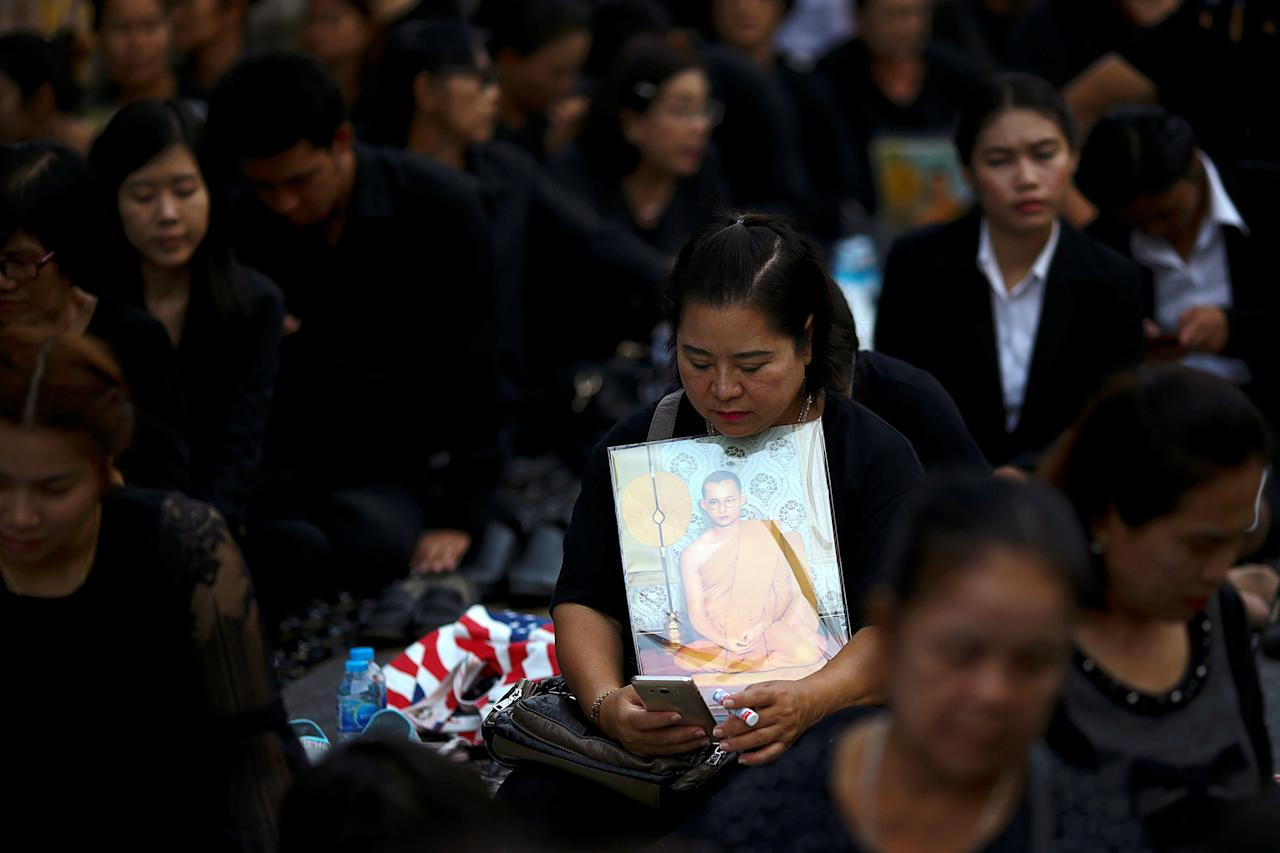 A mourner holds up a picture of Thailand's late King Bhumibol Adulyadej as she waits in line to offer condolences at the Grand Palace in Bangkok, Thailand, October 18, 2016. REUTERS/Athit Perawongmetha     TPX IMAGES OF THE DAY
