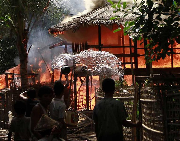 A person throws a bucket of warter at a house engulfed in flames in Sittwe, Myanmar, Monday, June 11, 2012. With fearful residents cowering indoors, security forces patrolling a tense town in western Myanmar collected bodies Monday from the debris of homes burned down over the weekend in some of the country's deadliest sectarian bloodshed in years. The Buddhist-Muslim violence, which has left at least seven people dead and hundreds of homes torched since Friday, poses one the biggest tests yet for Myanmar's new government as it struggles to reform the nation after generations of military rule. (AP Photo/Kihn Maung Win)