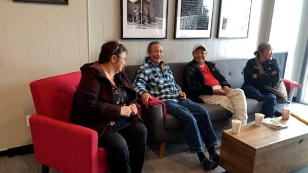 Melaine Norwegian, left, shares a laugh with other evacuees from Jean Marie River in the hotel lobby.