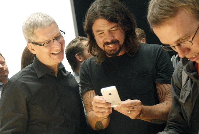 FILE -In this Wednesday, Sept. 12, 2012, file photo, Apple CEO Tim Cook, left, talks with musician Dave Grohl of the Foo Fighters as they look at an iPhone 5 during an Apple event in San Francisco. Apple is emerging as a gentler, cuddlier corporate citizen in the year after the death of CEO and co-founder Steve Jobs. CEO Tim Cook's announcement that the company is moving a Mac production line to the U.S. is just the latest step in a charm offensive designed to soften Apple's image. (AP Photo/Jeff Chiu)