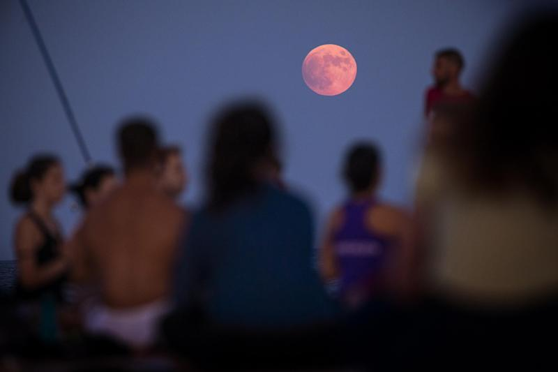 People take part in a yoga class in front of the partial lunar eclipse in Barcelona (AP)