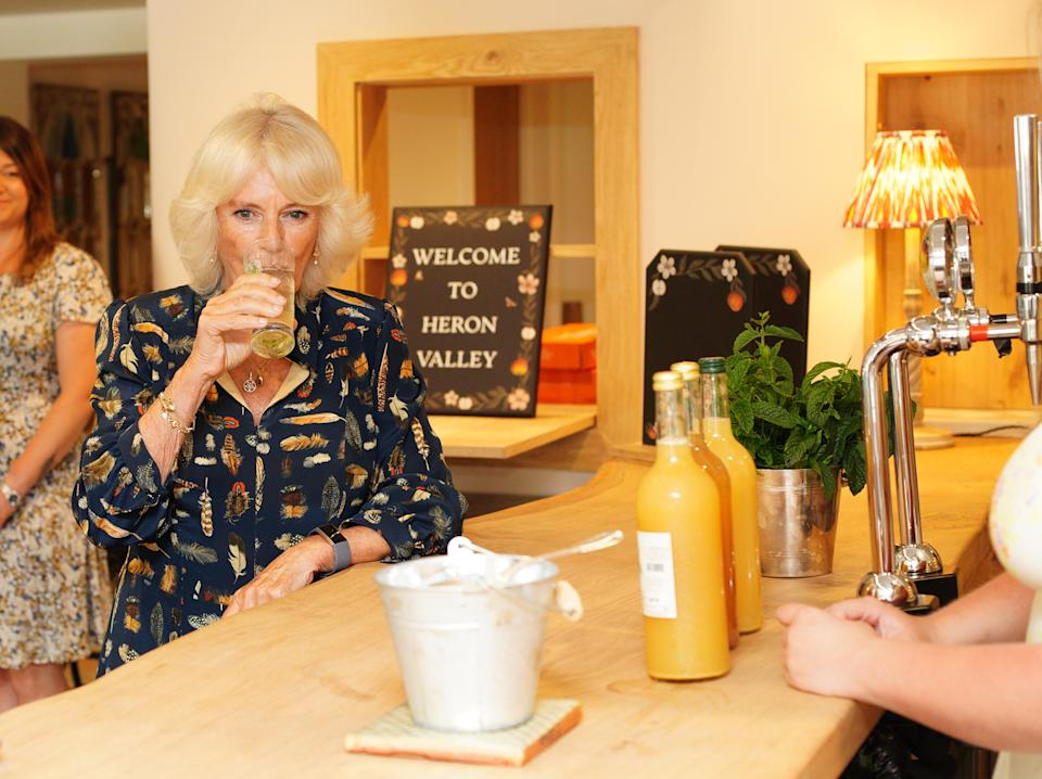 The Duchess of Cornwall drinking elderflower cordial during a visit to the new Weaver Green showroom at Heron Valley Orchards, in Loddiswell, Devon, to learn how the company creates homewares from recycled plastics and meet local school children learning about wildlife and sustainability. Picture date: Monday July 19, 2021.