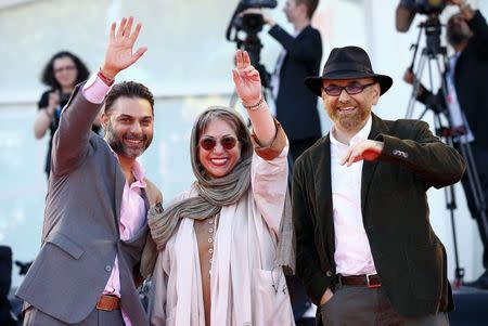 """Director Banietemad and actors Rezaei and Moadi wave as they arrive at the red carpet for the movie """"Ghesseha (Tales)"""" at the 71st Venice Film Festival"""