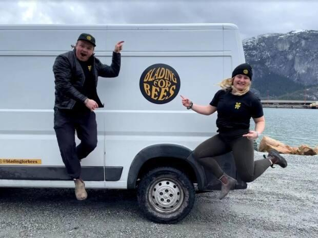Zachariah and Rachel Choboter take a leap in front of the 'Blading for Bees' van. (Submitted by Zachariah Choboter - image credit)