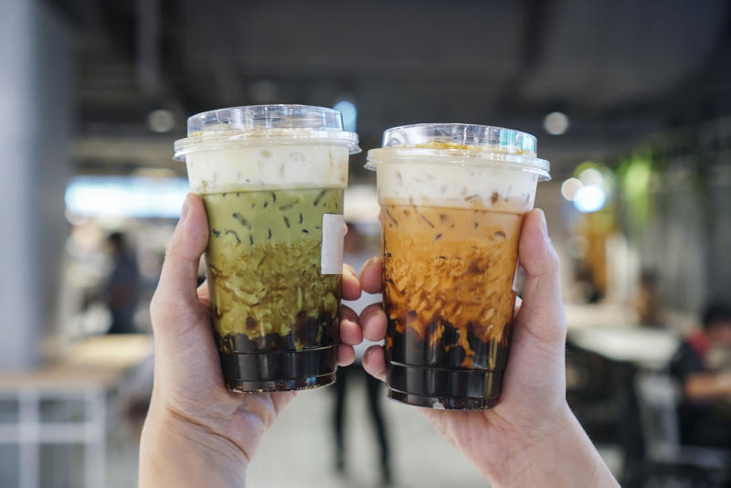 Man holding a plastic cup of bubble/boba matcha green tea and Thai tea with brown sugar and topped with cheese cream.