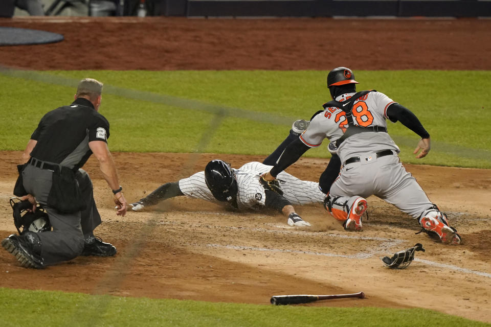 New York Yankees pinch runner Mike Tauchman scores a game-tying run as Baltimore Orioles catcher Pedro Severino (28) applies a late tag in the eighth inning of a baseball game, Wednesday, April 7, 2021, at Yankee Stadium in New York. (AP Photo/Kathy Willens)