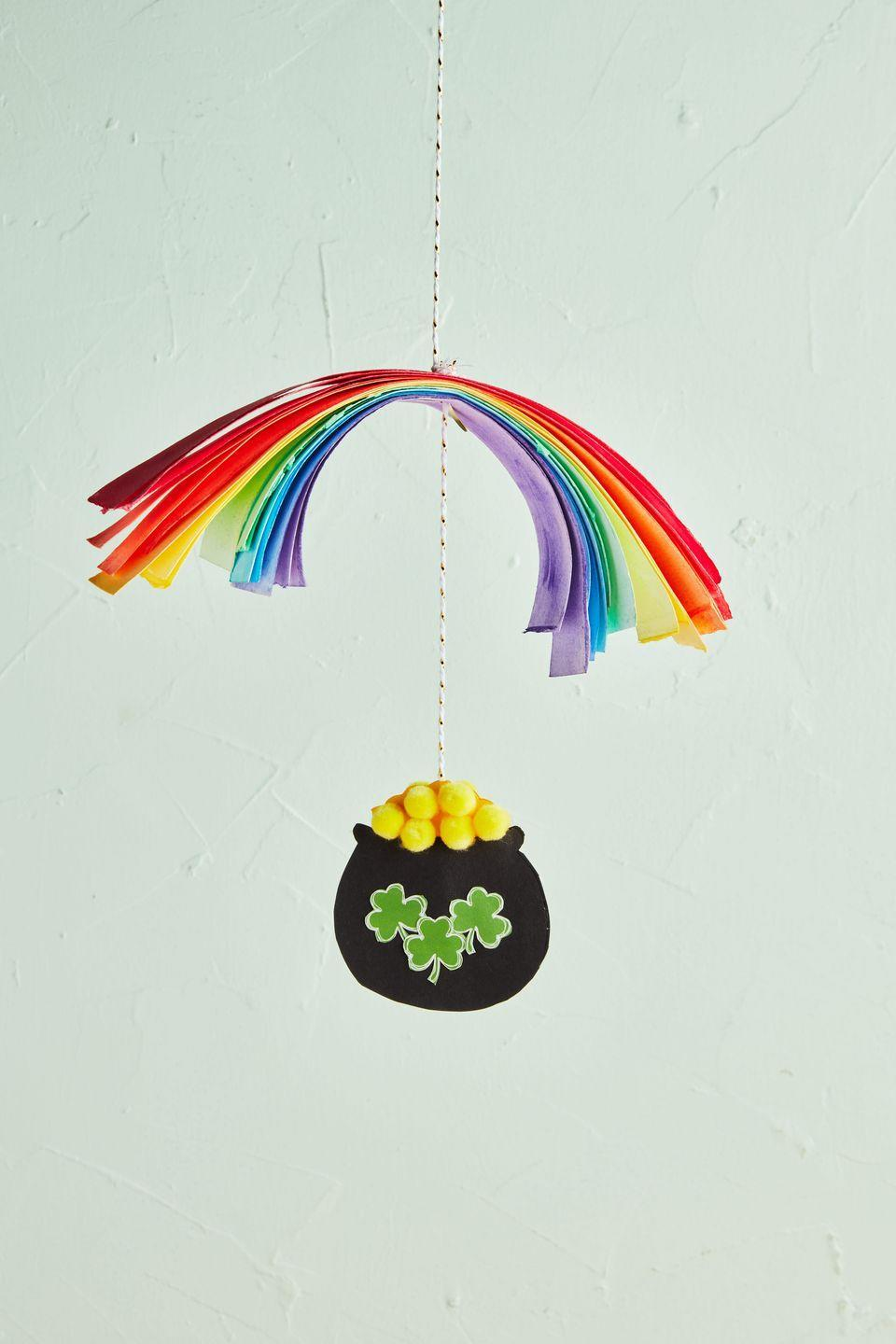 """<p>Gold, or mini yellow pom-poms? Either way, craft this DIY hanging mobile and lots of luck and riches will surely come your way!<br><br><strong>To make:</strong> Cut 1-inch-wide strips of paper from colored craft paper. Use a hole-punch to make a hole in the middle of each strip of paper; stack paper in the order of the rainbow. Thread a piece of twine through holes, knotting it just above and below the paper to hold paper in place. Fold a piece of black craft paper in half and cut out a pot shape, so that you have two identical pieces. Cut out two dome-shaped pieces of yellow craft paper and sandwich between the black pieces, gluing everything together. Glue mini yellow pom-poms to the yellow paper. Punch a hole at the top of the yellow dome, and thread twine through, securing with a knot. Cut out mini clovers from green craft paper and glue to the front and back of the pot; outline with a white pen if desired.<br><br><a class=""""link rapid-noclick-resp"""" href=""""https://www.amazon.com/Sheets-Origami-Colors-Stationery-Perfect/dp/B07P53JWP6/ref=sr_1_1?tag=syn-yahoo-20&ascsubtag=%5Bartid%7C10050.g.4035%5Bsrc%7Cyahoo-us"""" rel=""""nofollow noopener"""" target=""""_blank"""" data-ylk=""""slk:SHOP PAPER"""">SHOP PAPER</a></p>"""