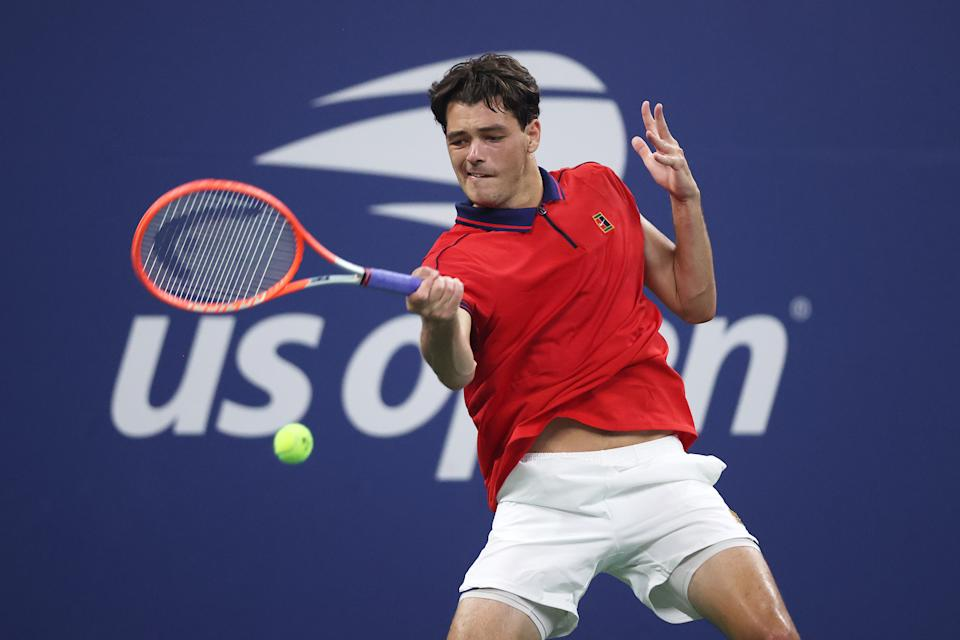 Pictured here, Taylor Fritz returns the ball against Alex de Minaur during their US Open clash.