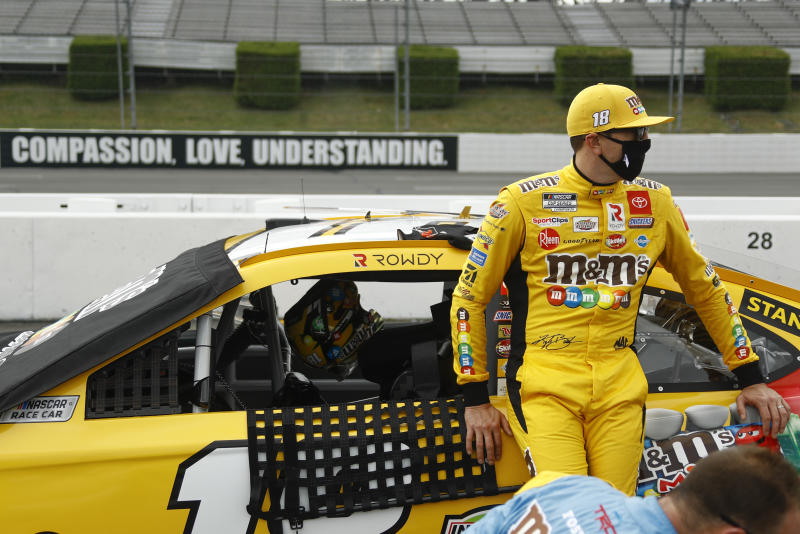 Kyle Busch leans on his car before the start of the NASCAR Cup Series auto race at Pocono Raceway, Sunday, June 28, 2020, in Long Pond, Pa. (AP Photo/Matt Slocum)