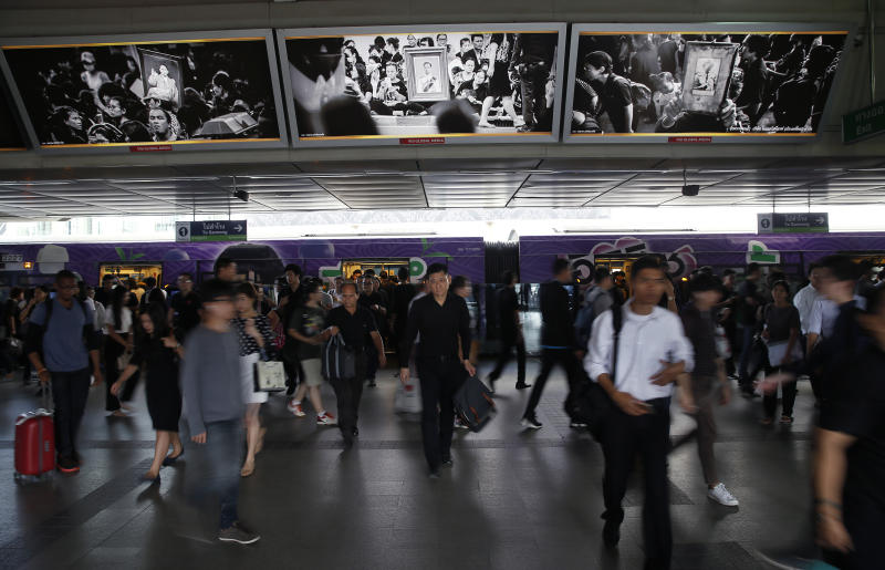 In this Monday, Oct. 16, 2017, photo, Skytrain passengers dressed primarily in black come and go under black and white images in memory of the late King of Thailand at a station platform in Bangkok, Thailand. The muted colors of mourning have settled over Bangkok once again in recent weeks as the country marks a year since the death of its beloved monarch, King Bhumibol Adulyadej, and prepares for the national spectacle of his cremation next week. (AP Photo/Wally Santana)