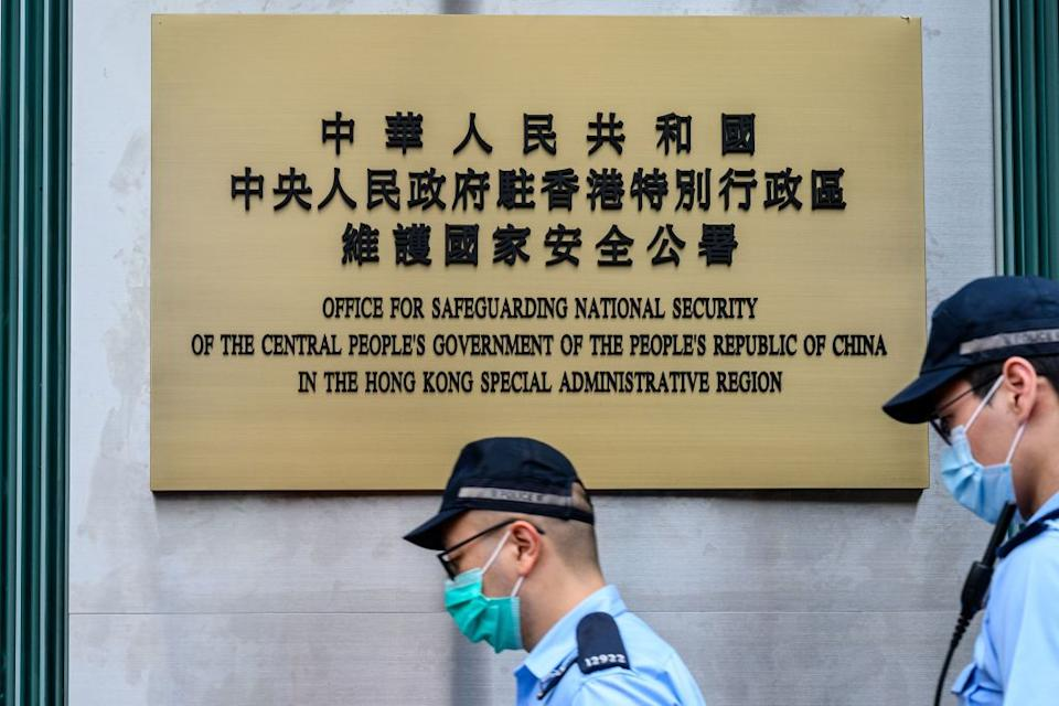 Police walk past the Office for Safeguarding National Security of the Central People's Government in the Hong Kong after its official inauguration on July 8, 2020. | Anthony WALLACE—AFP/Getty Images