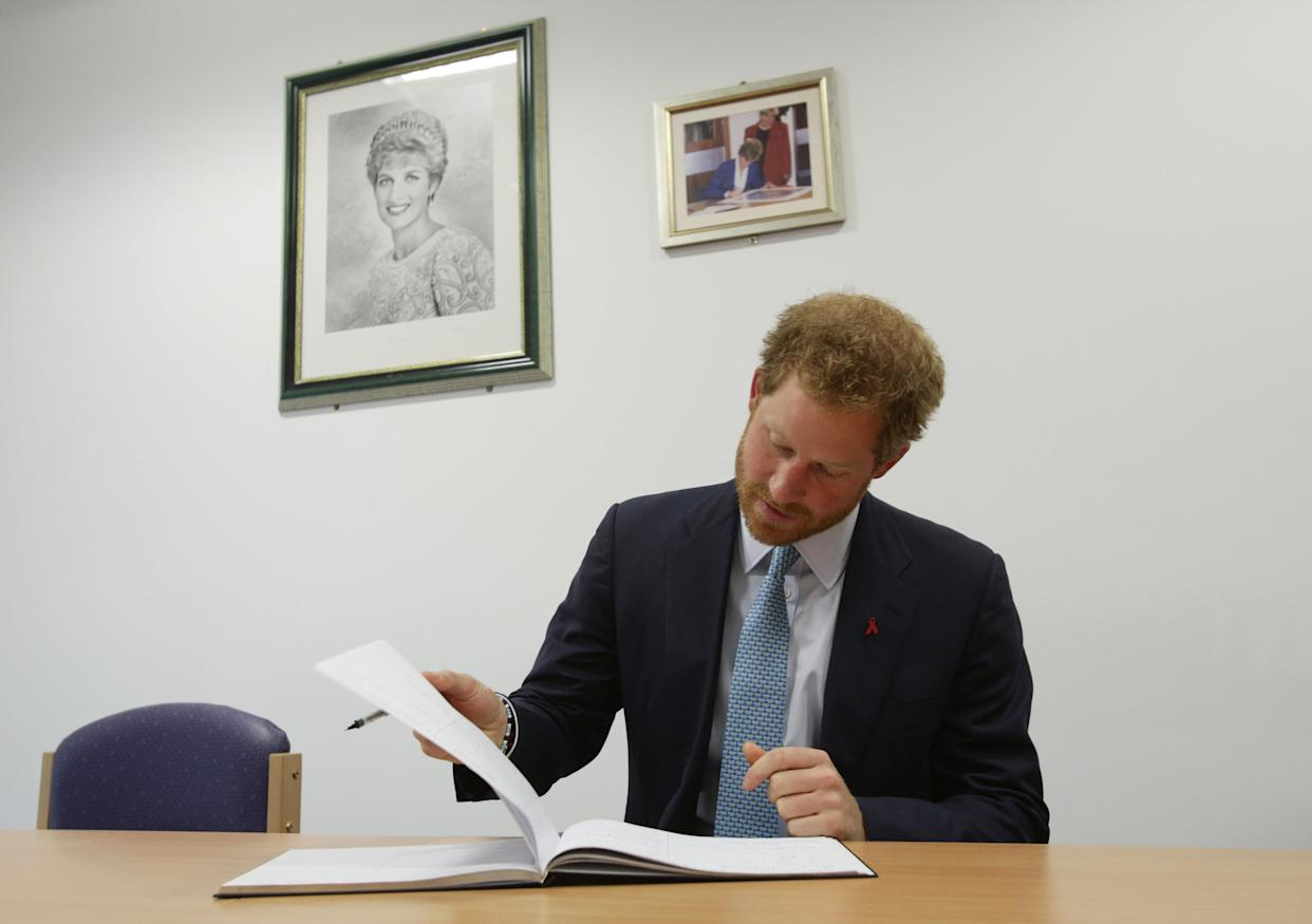 LONDON, ENGLAND - DECEMBER 14: Prince Harry signs the visitors book during a visit to Mildmay hospital, a dedicated HIV hospital, to mark the opening of the new purpose built facility at Mildmay Hospital on December 14, 2015 in London, England.  (Photo by Yui Mok-WPA Pool/Getty Images)