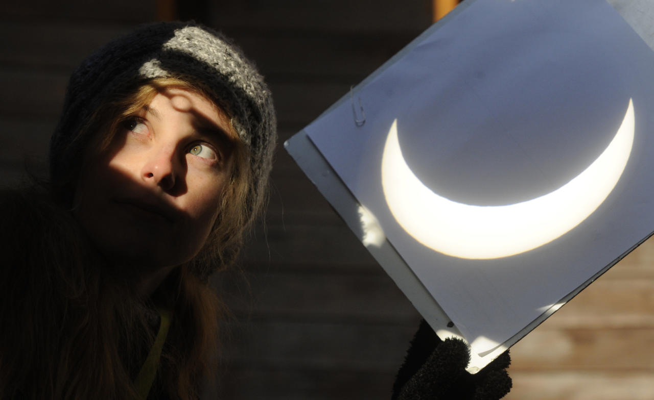 An unidentified employee of the Stefanik Observatory in Prague uses a projection shield to show the partial solar eclipse visible in the Czech capital during the morning on Tuesday, Jan. 4, 2011.  The partial eclipse started over the Czech Republic at about 08:00 CET and will last until 10:50. In the culminating phase, up to 80 percent of the solar disc was obscured by the silhouette of the moon passing between it and the earth. (AP Photo/CTK, Michal Kamaryt)  Slovakia Out