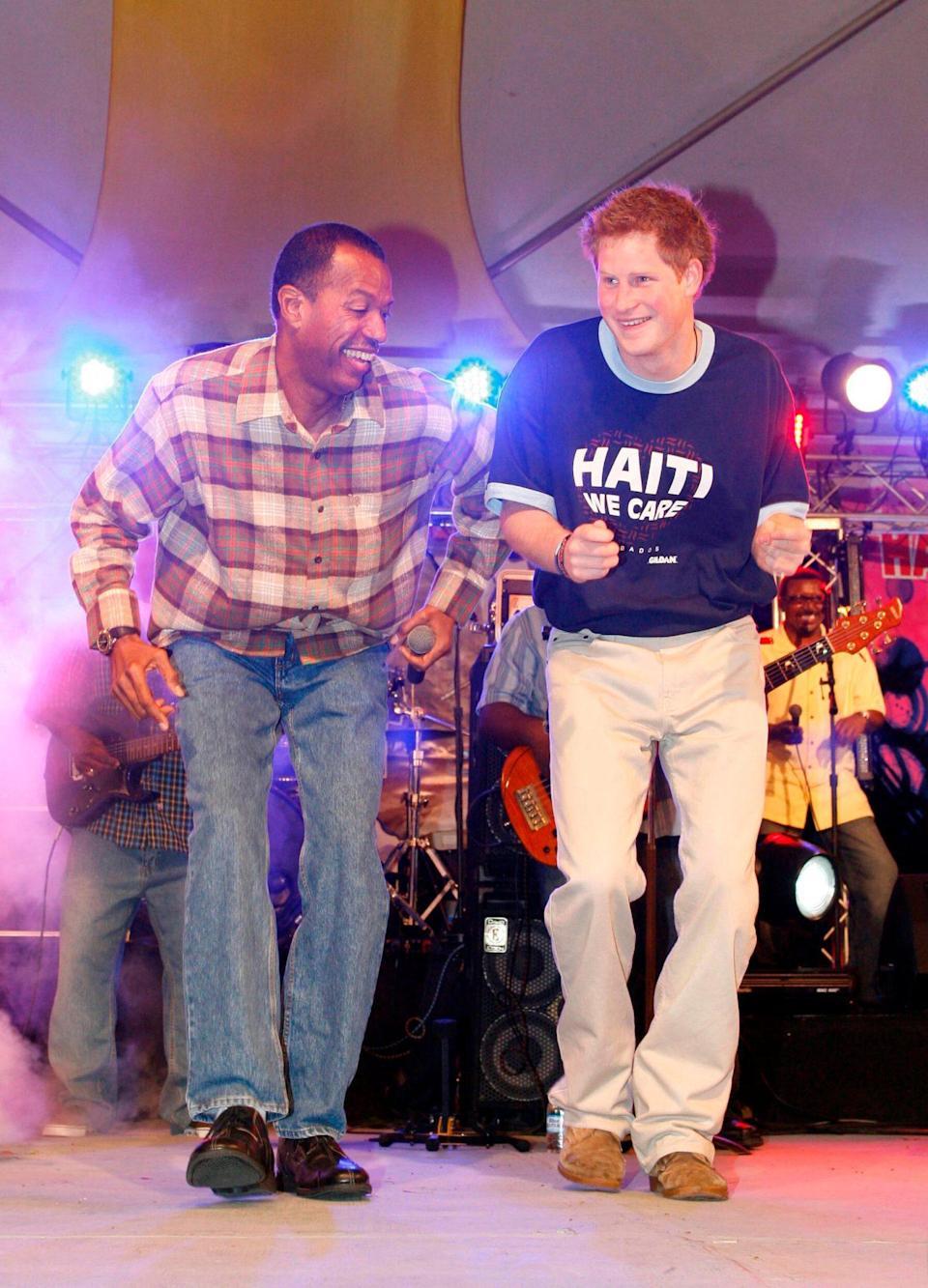 """<p>In 2010, a then-25-year-old Prince Harry wore his mission on his """"Haiti We Care"""" T-shirt at a fundraising concert for victims of a devastating earthquake. Gamely volunteering to show the crowd — including viewers on television in Barbados — his moves for a charitable donation, Harry eventually took to the stage to try his hand (and hips!) at a calypso dance.</p>"""