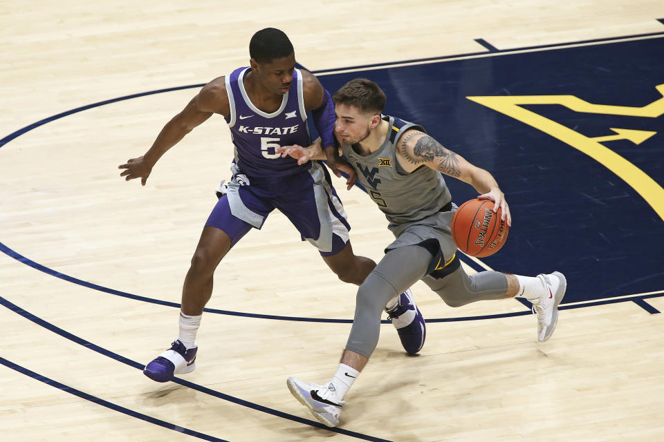 West Virginia guard Jordan McCabe (5) is defended by Kansas State guard Rudi Williams (5) during the first half of an NCAA college basketball game Saturday, Feb. 27, 2021, in Morgantown, W.Va. (AP Photo/Kathleen Batten)