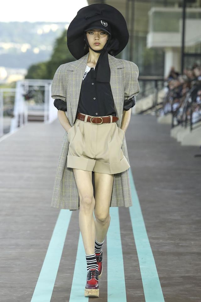 """<p>Miu Miu showed at the Bois de Boulogne in Paris—a racetrack that dates back to 1873. This charming set up, at sunset no less, served as backdrop to a collection that emphasized color, volume, and a great pair of shorts. 1930s inspired dresses with exaggerated details like oversized collars walked alongside """"Newsies""""-worthy short suits with the hats to match. Grandpa cardigans, striped ankle socks, and saddle bags complete the idea—which was an overall charming look at life at the track. <br><br></p>"""