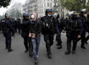 Police detain a protestor during a demonstration in Paris, France, Saturday, July 31, 2021. Demonstrators gathered in several cities in France on Saturday to protest against the COVID-19 pass, which grants vaccinated individuals greater ease of access to venues. (AP Photo/Adrienne Surprenant)