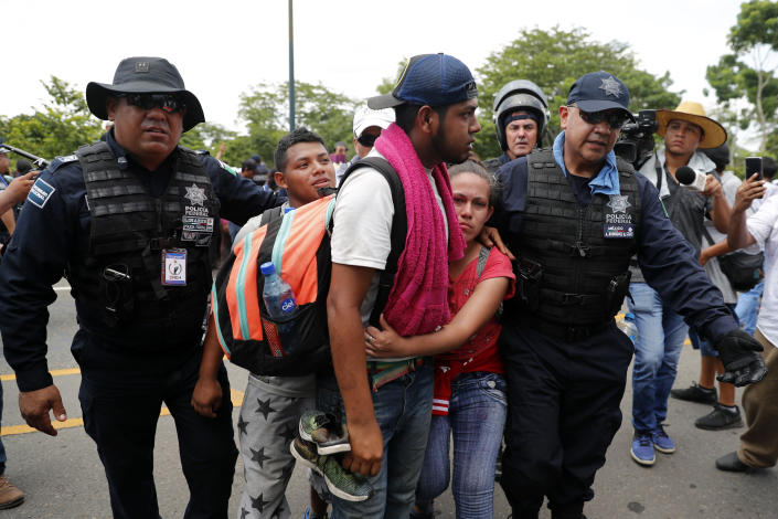 Migrants are detained by Mexican immigration authorities during a raid on a migrant caravan that had earlier crossed the Mexico - Guatemala border, near Metapa, Chiapas state, Mexico, Wednesday, June 5, 2019. U.S. President Donald Trump has pledged to impose 5% tariffs on Mexican products unless Mexico country prevents Central American migrants from traveling through its territory.(AP Photo/Marco Ugarte)