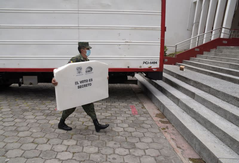 A soldier carries cardboard for ballot boxes at a polling station ahead of Ecuador's presidential election on February 7, in Quito