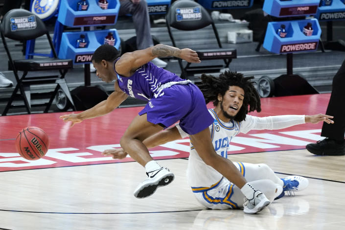Abilene Christian's Damien Daniels, left, and UCLA's Tyger Campbell, right, battle for a loose ball during the first half of a college basketball game in the second round of the NCAA tournament at Bankers Life Fieldhouse in Indianapolis Monday, March 22, 2021. (AP Photo/Mark Humphrey)