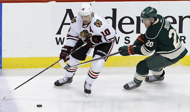 Chicago Blackhawks left wing Patrick Sharp (10) and Minnesota Wild defenseman Ryan Suter (20) chase the puck during the first period of an NHL hockey game in St. Paul, Minn., Thursday, Dec. 5, 2013. (AP Photo/Ann Heisenfelt)