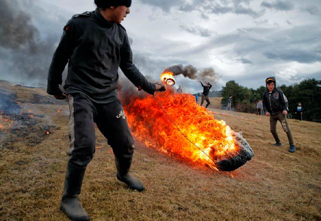 In this photo taken on Sunday, March 10, 2019, children spin burning tires during a ritual marking the upcoming Clean Monday, the beginning of the Great Lent, 40 days ahead of Orthodox Easter, on the hills surrounding the village of Poplaca, in central Romania's Transylvania region. Romanian villagers burn piles of used tires then spin them in the Transylvanian hills in a ritual they believe will ward off evil spirits as they begin a period of 40 days of abstention, when Orthodox Christians cut out meat, fish, eggs, and dairy. (AP Photo/Vadim Ghirda)