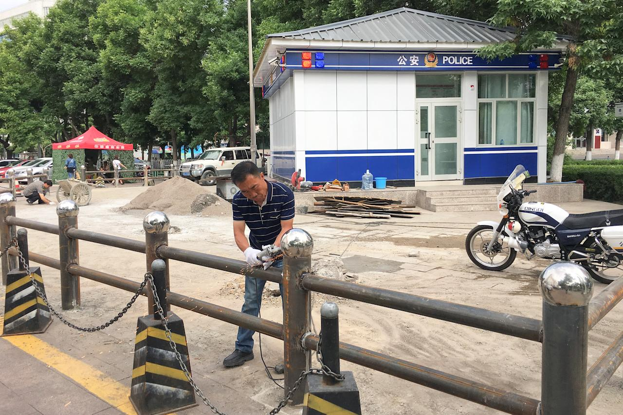 A man installs fencing in front of a police station in Yili, Xinjiang Province, China May 17, 2017. Picture taken May 17, 2017. REUTERS/Sue-Lin Wong