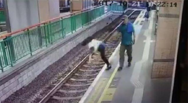 CCTV shows the man pushing the woman onto the tracks. Source: Facebook