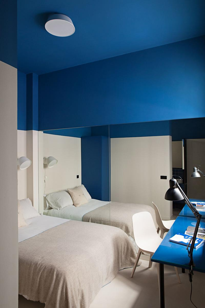 """After: Ana and Enrique installed wall-to-wall mirror on one side of the smallest bedroom in the apartment, the """"Blue and Beige Room,"""" to open it up."""