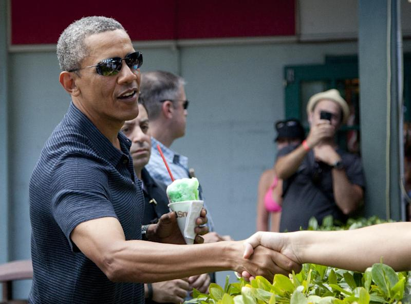 President Barack Obama shakes hands with people waiting to meet him as he holds his shave ice outside Island Snow, Tuesday, Dec. 31, 2014. The first family is in Hawaii for their annual holiday vacation. (AP Photo/Carolyn Kaster)