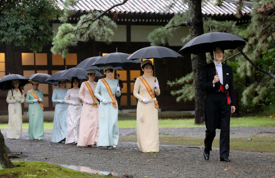 """Japan's Crown Prince Akishino, right, and Crown Princess Kiko, second from right, arrive for the ceremony at """"Kashikodokoro"""", one of three shrines at the Imperial Palace, in Tokyo, Tuesday, Oct. 22, 2019. Emperor Naruhito and Empress Masako visited three Shinto shrines at the Imperial Palace before Naruhito proclaims himself Japan's 126th emperor in an enthronement ceremony. (Kyodo News via AP)"""