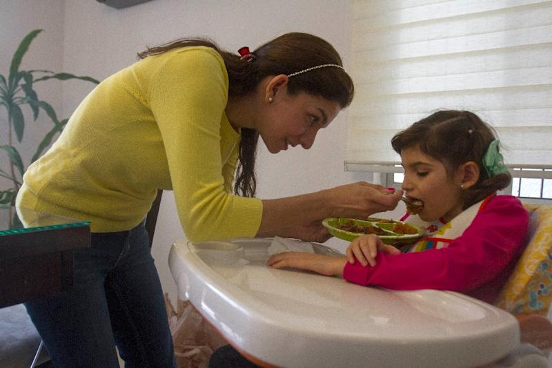 Grace with her mother Mayela Benavides at their house on November 12, 2015 in the Guadalupe municipality (AFP Photo/Julio Cesar Aguilar)