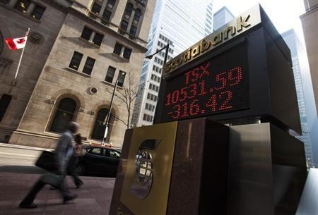 People walk by a sign displaying TSX information in Toronto