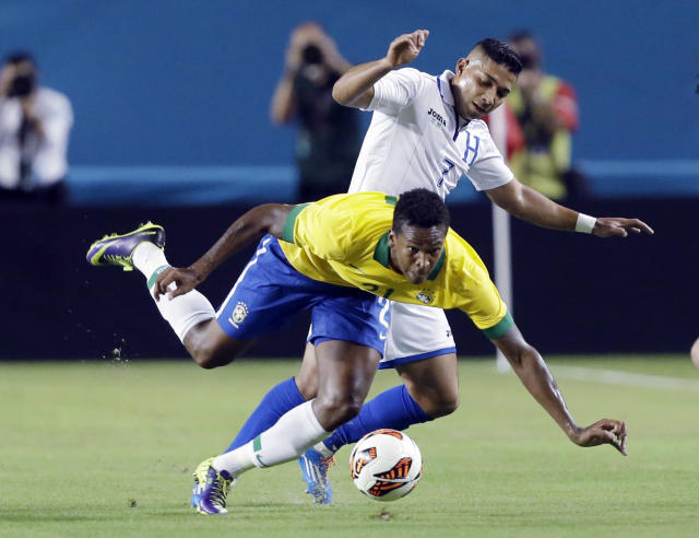 Brazil forward Jo, foreground, goes down as he battles for the ball with Honduras' Emilio Izaguirre during the first half of an international friendly soccer game, Saturday, Nov. 16, 2013, in Miami Gardens, Fla. (AP Photo/Wilfredo Lee)