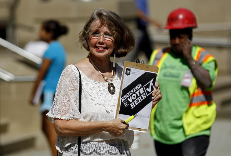 In this photo taken Wednesday, Sept. 26, 2012, campaign volunteer Barbara Smalley-McMahan attempts to register voters in downtown Raleigh, N.C. Dozens of volunteers armed with clipboards and voter registration forms gather at President Barack Obama's field office here every day. Their mission: Fan out across the city seeking new voters in this rapidly growing state. (AP Photo/Gerry Broome)