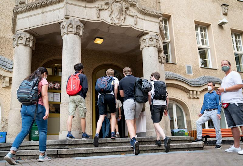 10 August 2020, Berlin: Students enter the entrance to the Rheingau Gymnasium on the first day after the summer holidays. In addition to Berlin, classes also start in Brandenburg and Schleswig-Holstein. Photo: Kay Nietfeld/dpa (Photo by Kay Nietfeld/picture alliance via Getty Images)