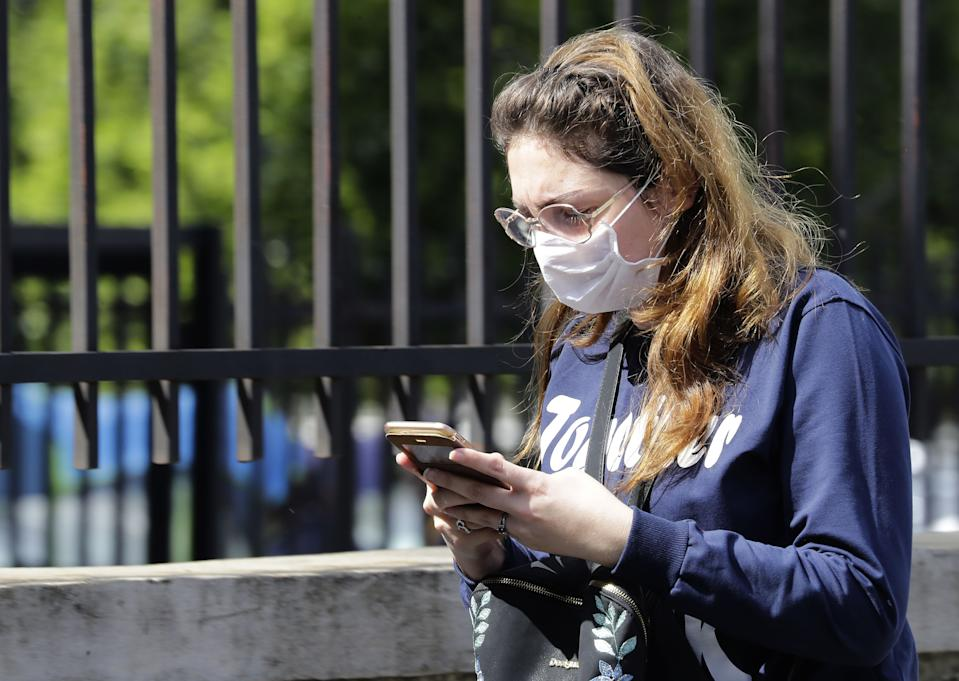 A Lebanese woman wears a surgical mask as protection from the novel coronavirus outbreak, while she checks her phone in the capital Beirut, on March 2, 2020. - Lebanon announced on February 28, it would bar entry to non-resident foreigners from the four countries most affected by the COVID-19 epidemic, a day after announcing its third case. (Photo by JOSEPH EID / AFP) (Photo by JOSEPH EID/AFP via Getty Images)