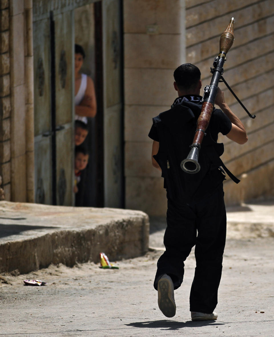 A Free Syrian Army fighter walks with a rocket launcher moments before clashing with Syrian troops near Idlib, Syria, Friday, June 15, 2012. (AP Photo)