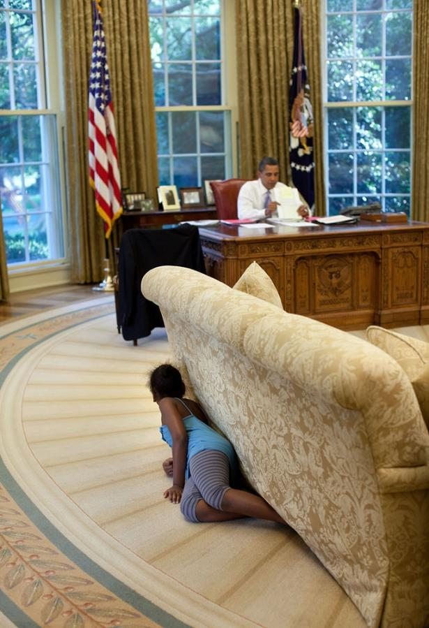 """""""I was sitting in the reception area outside the Oval Office on Aug. 5, 2009, when Sasha walked by and headed to the Oval. I suspected something was up, so I followed her. Sasha then crawled into the office, hiding behind the sofa, and when she reached the far end, jumped up and yelled, trying spook her dad."""" (Pete Souza / The White House) <br> <br> <a href=""""http://lightbox.time.com/2012/10/08/pete-souza-portrait-of-a-presidency/#1"""" rel=""""nofollow noopener"""" target=""""_blank"""" data-ylk=""""slk:Click here to see the full collection at TIME.com"""" class=""""link rapid-noclick-resp"""">Click here to see the full collection at TIME.com</a>"""